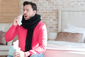 Flu epidemics. Sick unhappy bearded man holding a paper tissue and sneezing while sitting on the bed